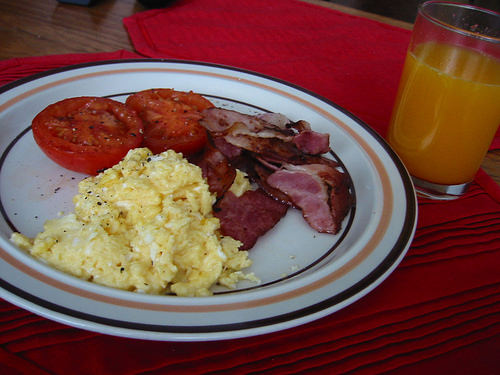 Bacon, scrambled eggs, fried tomato and freshly squeezed orange juice