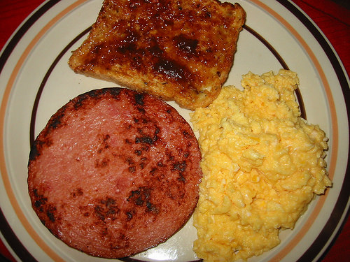 Fried ham steak, scrambled eggs and toast with strawberry spread