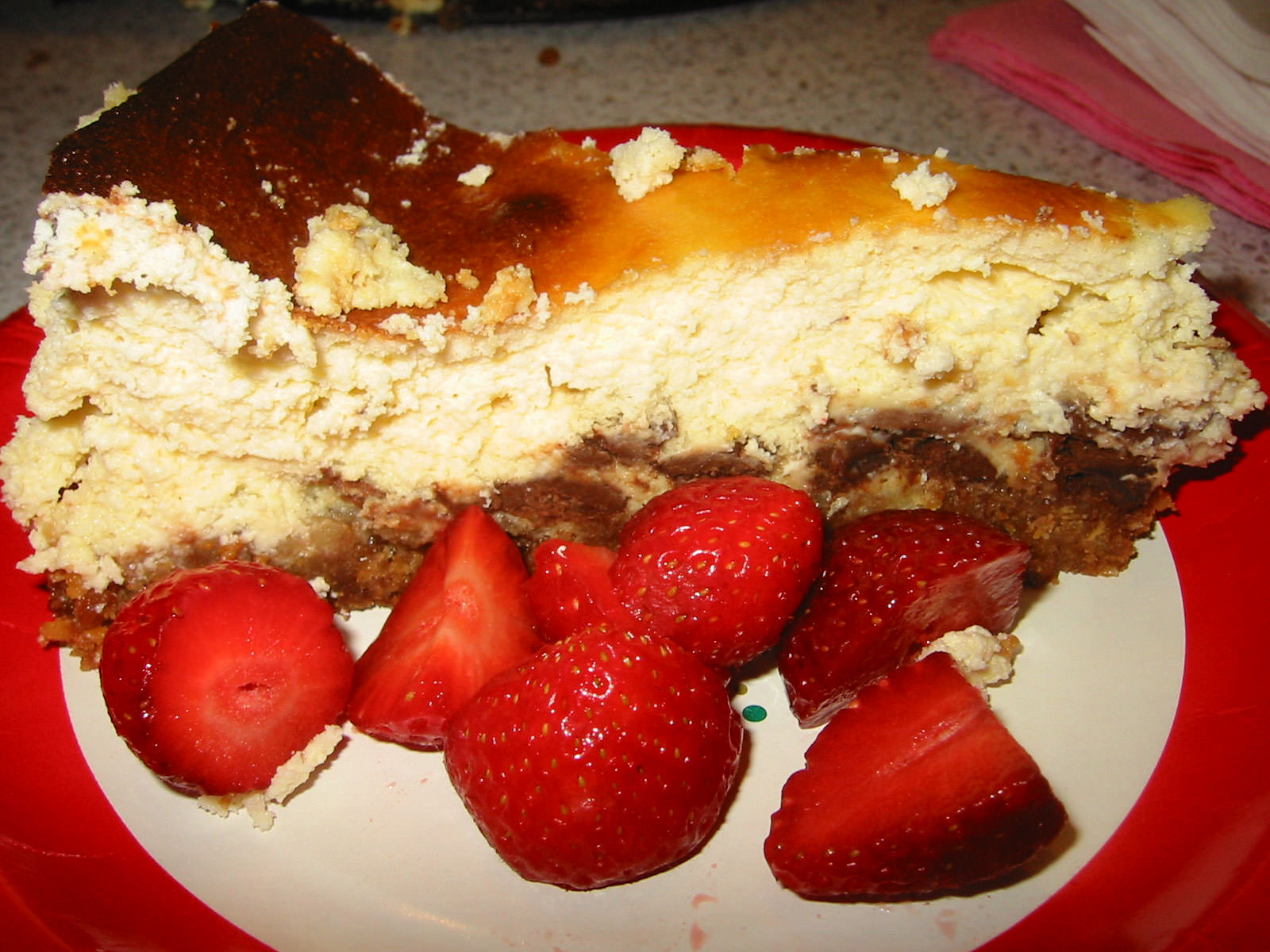 A slice of baked chocolate cheese cake with strawberries