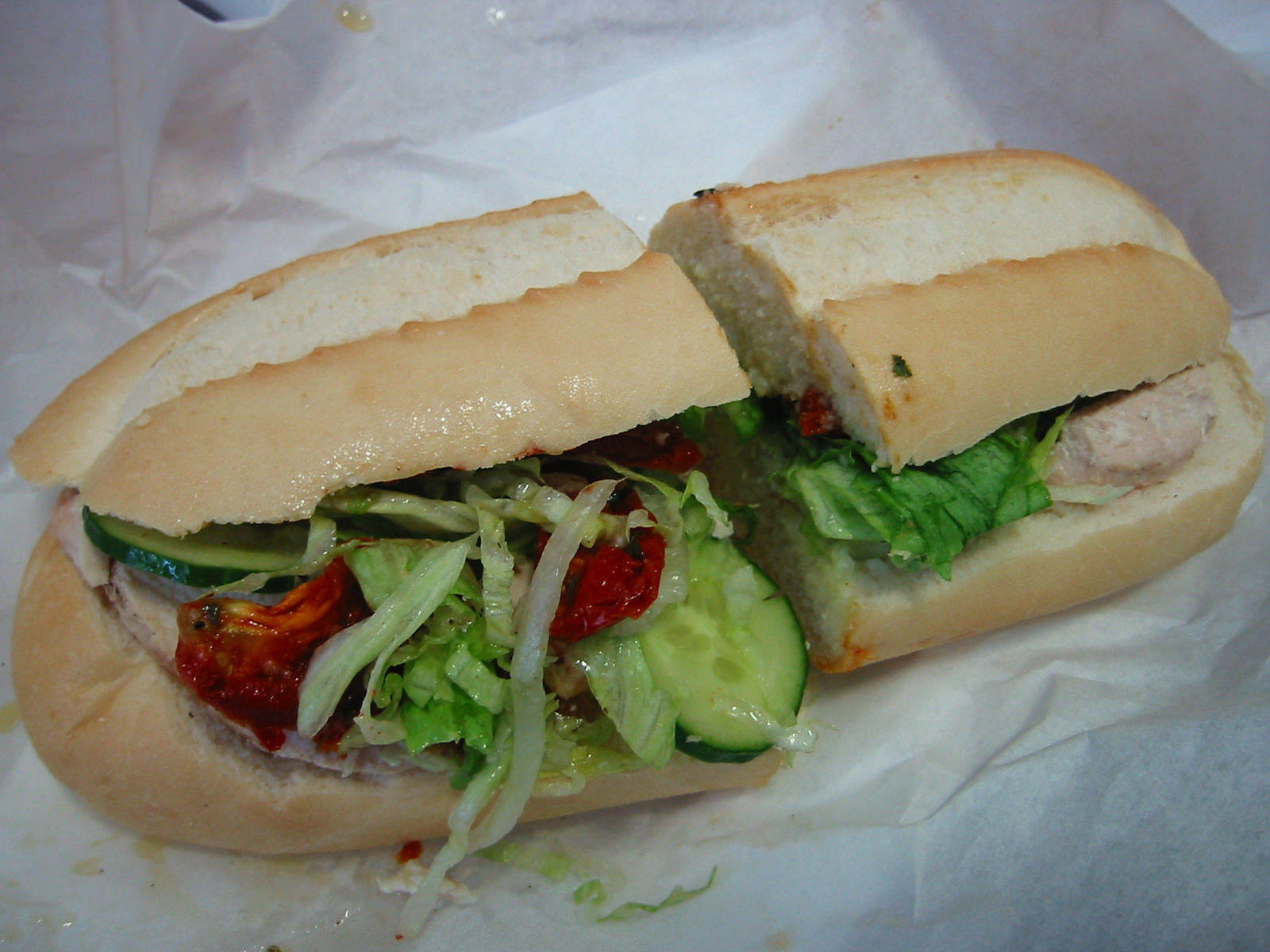 Bread roll with chicken, cucumber, lettuce and sundried tomatoes