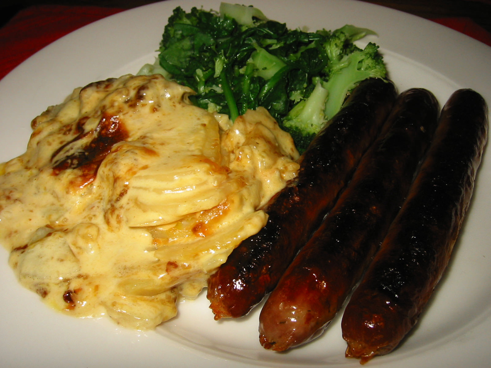 Sausages, potato bake and steamed broccoli and English spinach