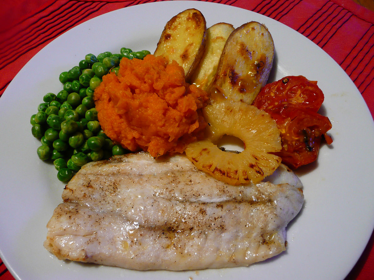Grilled snapper, grilled potatoes, tomato and pineapple, with orange mash and peas