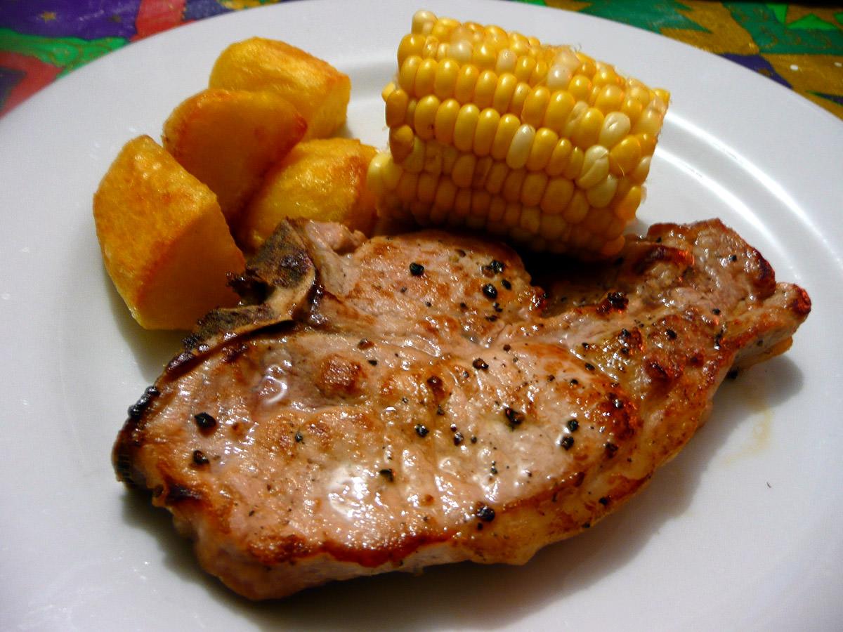 Pork chop, baked potatoes and corn