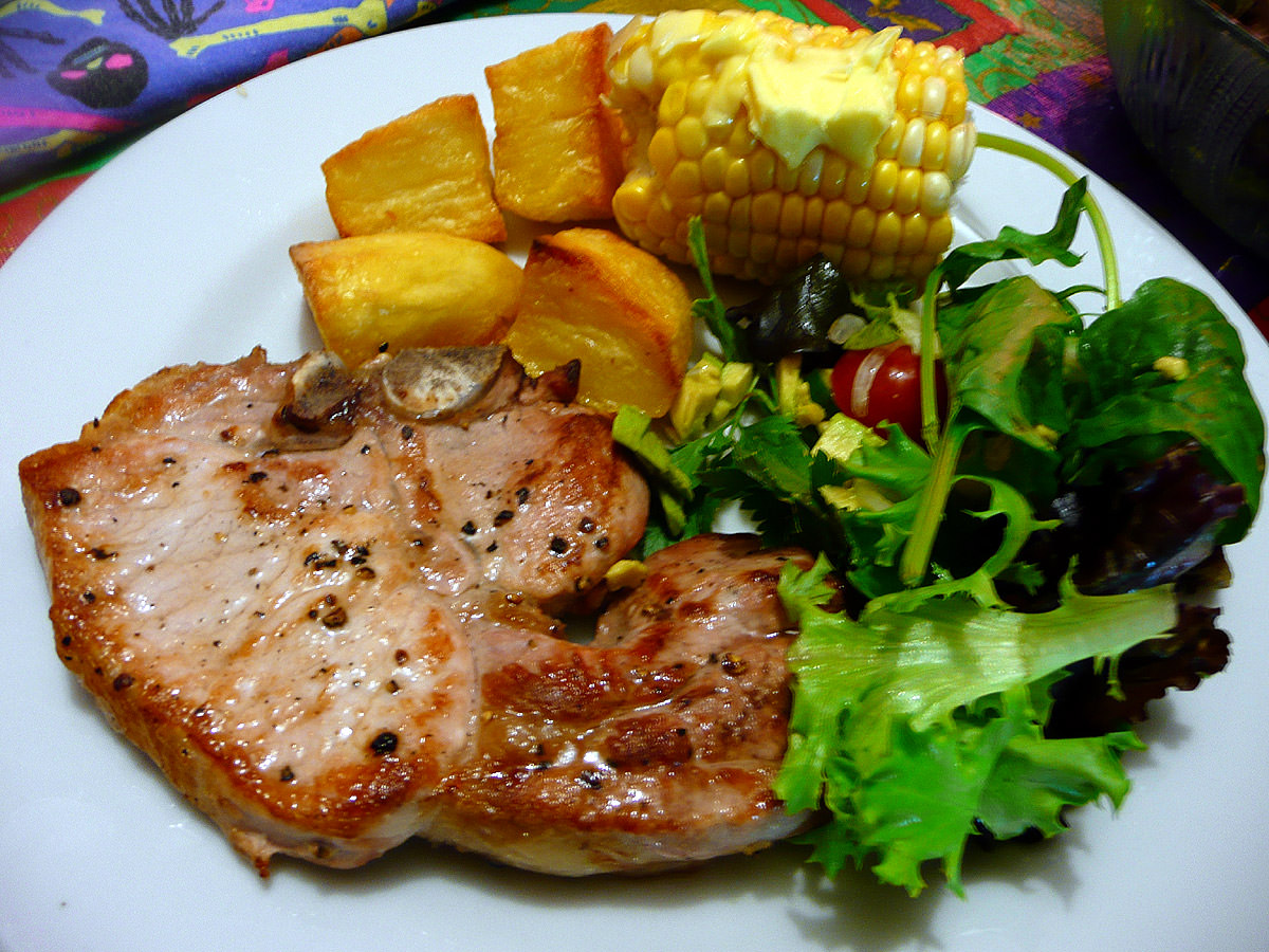 Pork chop, baked potatoes, salad and buttered corn