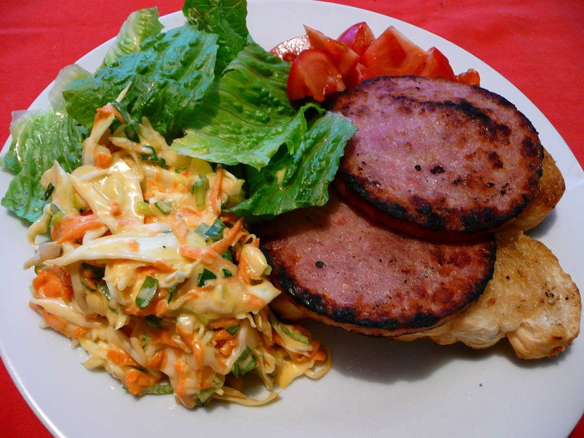 Ham steaks on garlic toast with salad and coleslaw