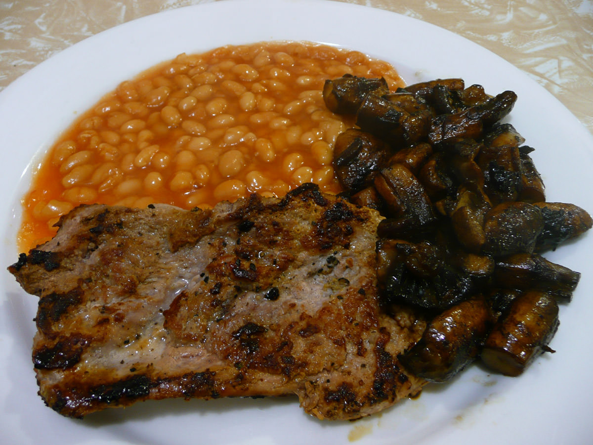 Fried turkey steak with baked beans and mushrooms