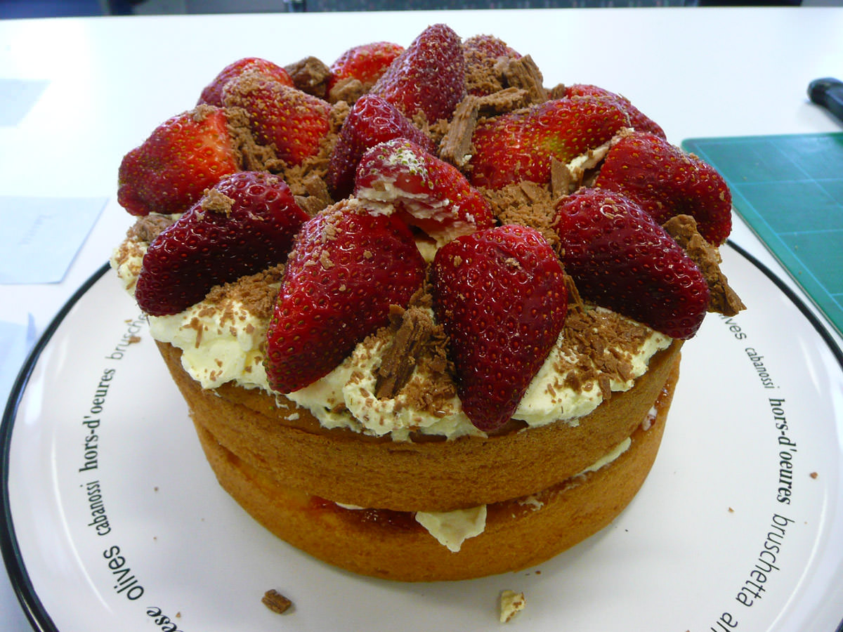 Two layers of sponge cake with cream, jam and strawberries