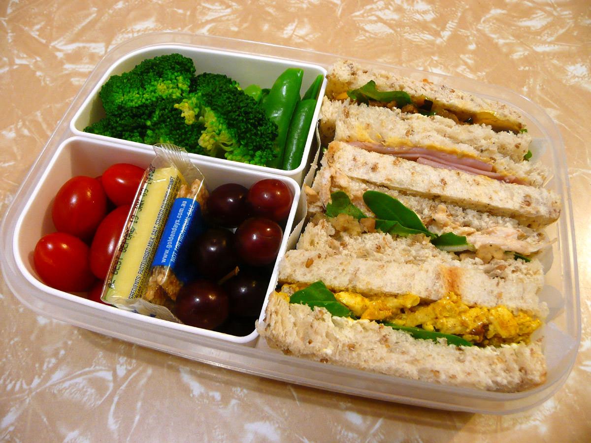 Bento - sandwiches, salad, fruit, cheese and mini sesame snaps