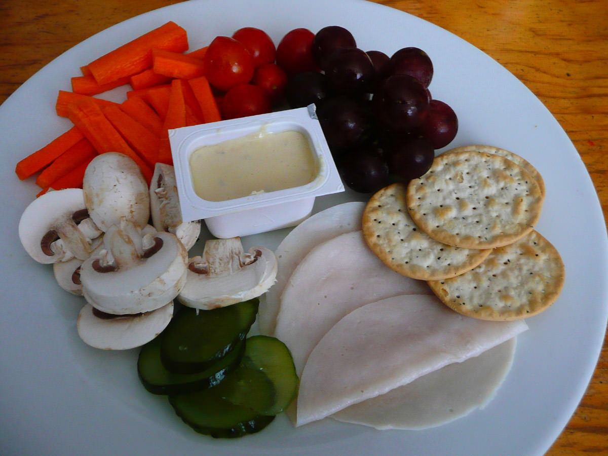 Crackers, vegetables, cold sliced turkey, pickles and French onion dip