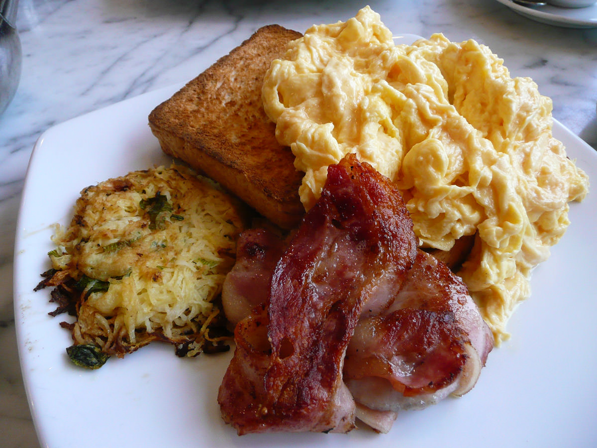 Scrambled eggs on toast, bacon and a horridly dry and burnt potato cake