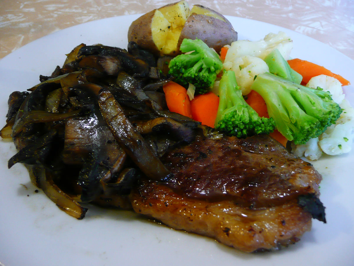 Porterhouse steak with onions and mushrooms, steamed vegetables and baked potato