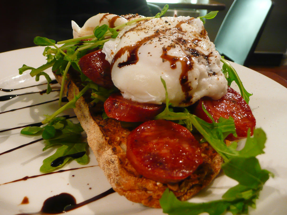 Poached eggs, fried chorizo and rocket on toast