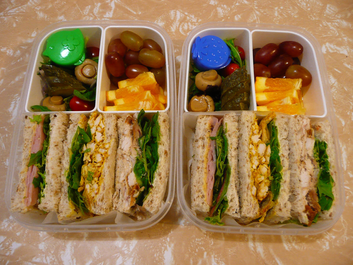 Two bento lunches - sandwiches, fruit and salad