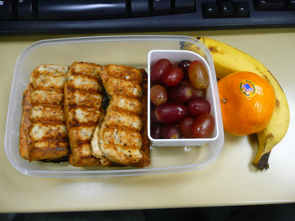 A sort of breakfast bento - toasted sandwiches and fruit