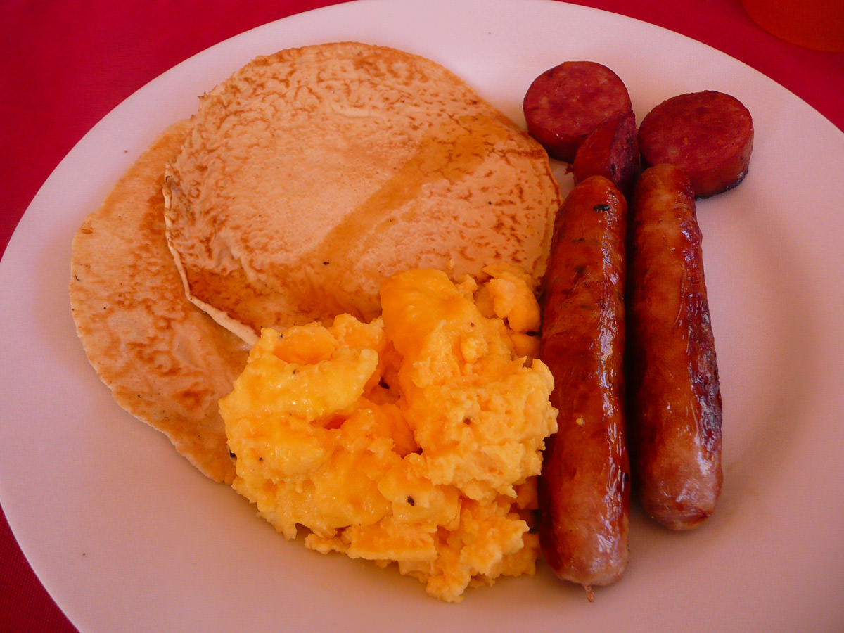 Leftover pancakes with maple syrup, sausage, scrambled eggs