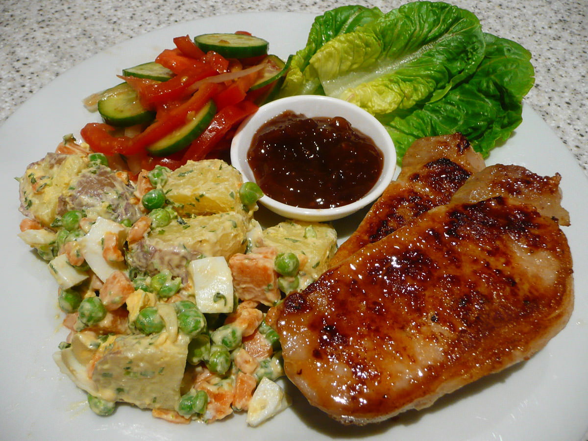 Pork Steaks With Potato Salad Tomato And A Dish Of Fruit Chutney
