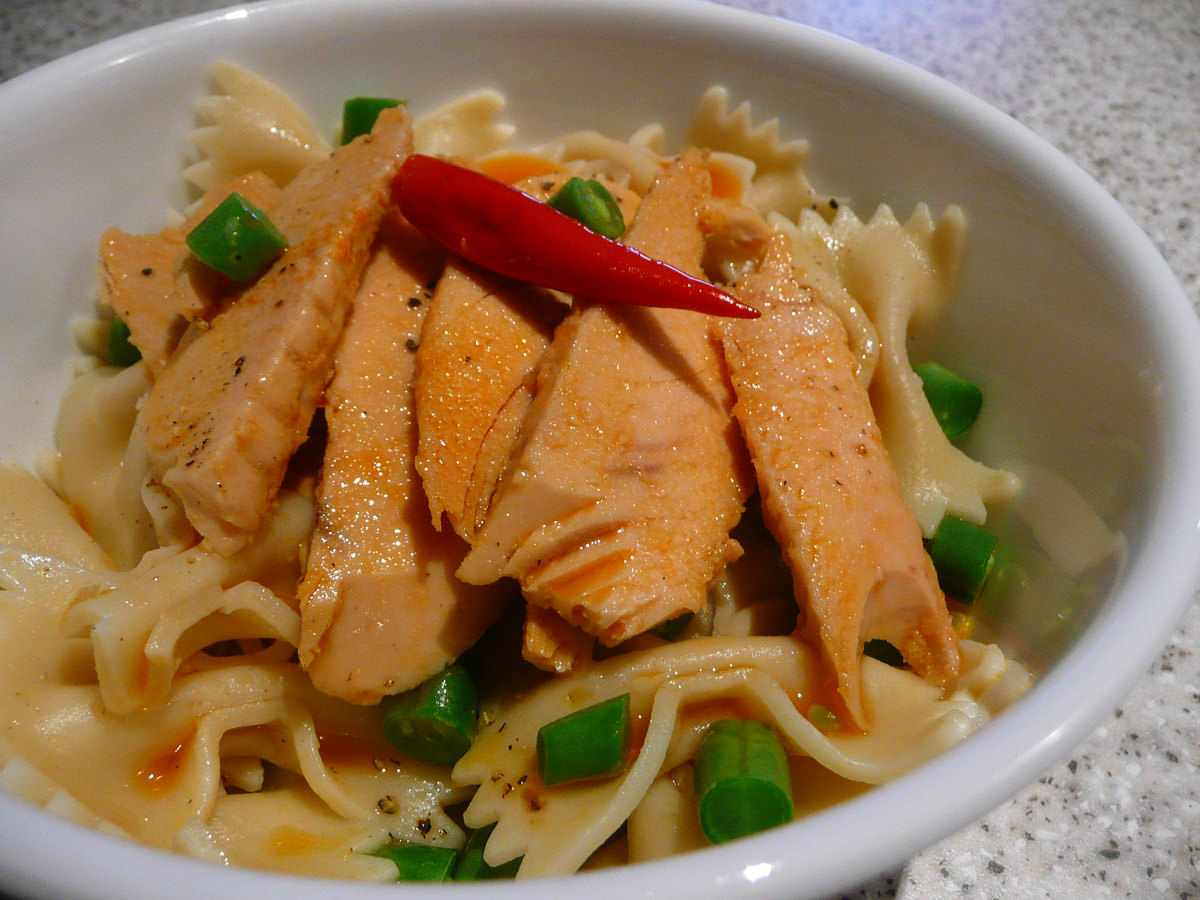 Tuna in chilli oil with bow pasta and green beans close-up