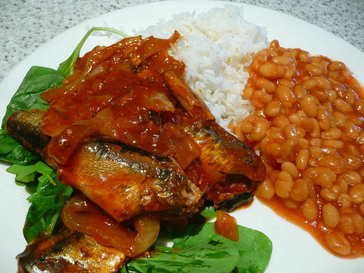 Sardines and onions in tomato sauce with rice, baked beans and salad