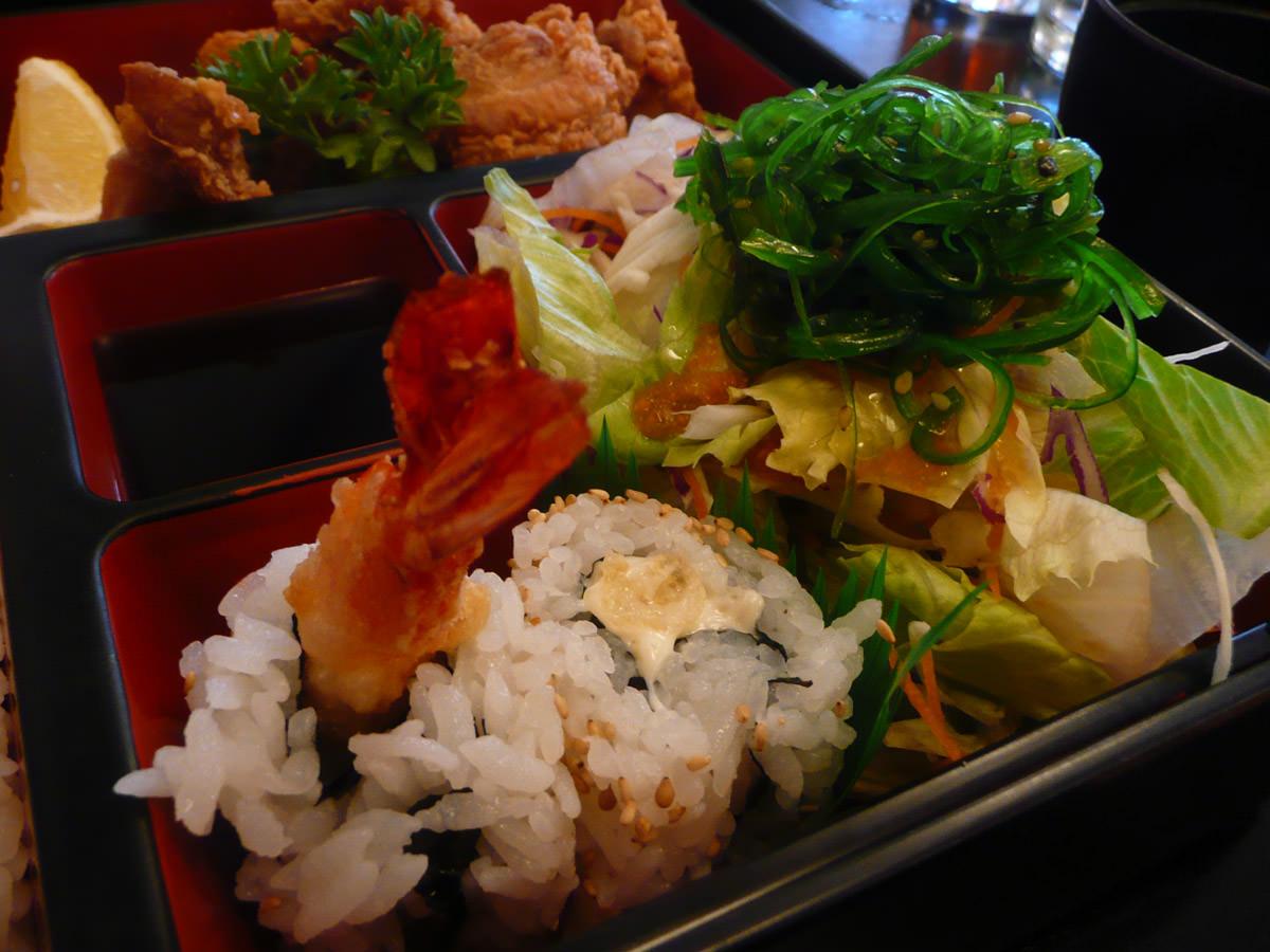 Teriyaki prawn sushi and salad topped with seaweed
