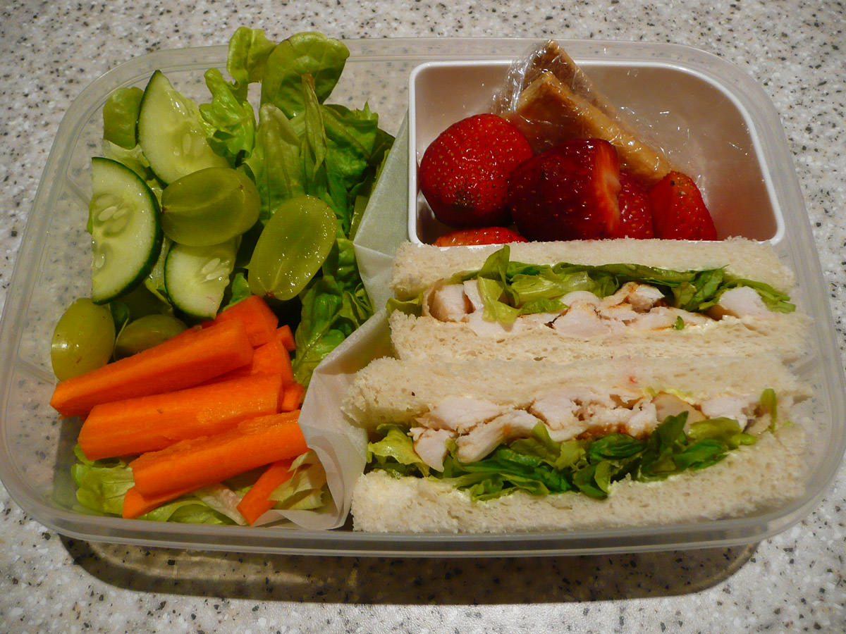 My bento lunch - Thai red curry chicken sandwiches, salad, strawberries and sweet crackers