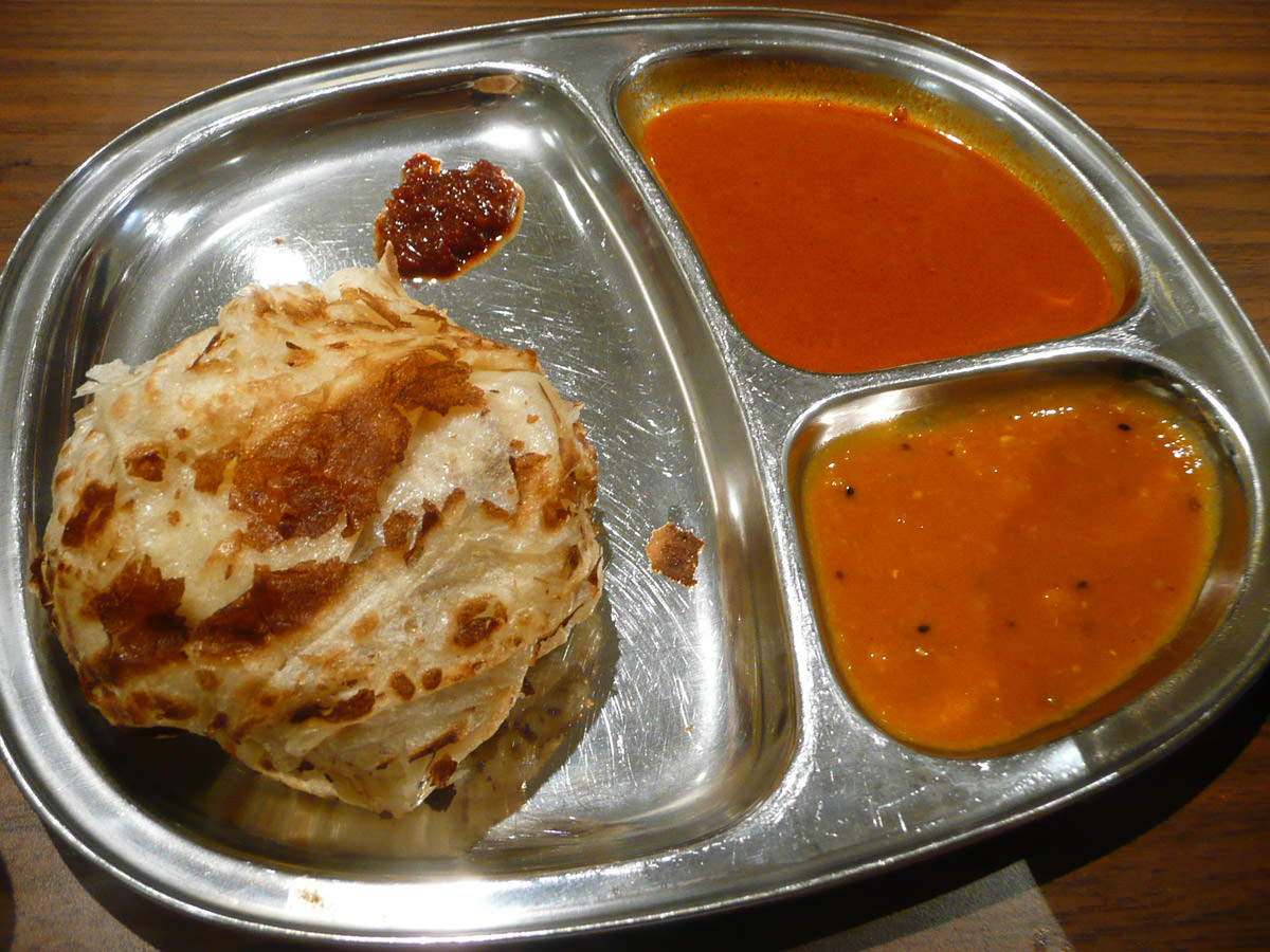 Roti canai with two curry gravies for dipping, and a little blob of sambal