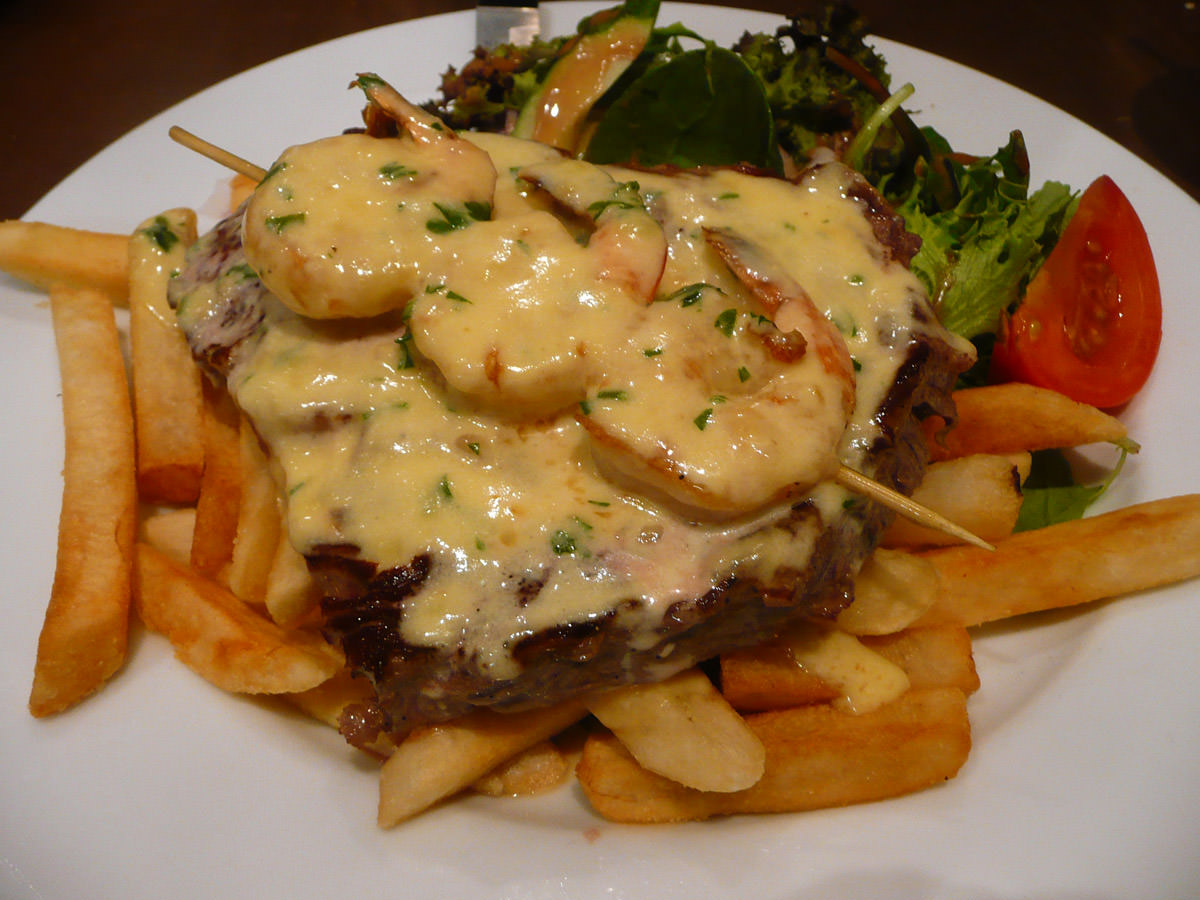 Scotch filet steak with prawns and creamy garlic sauce