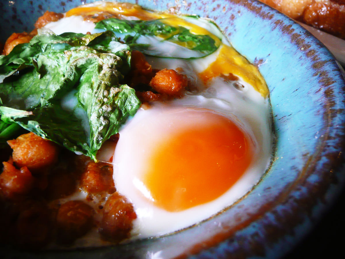 Baked eggs with spiced chickpeas and spinach - close-up of egg