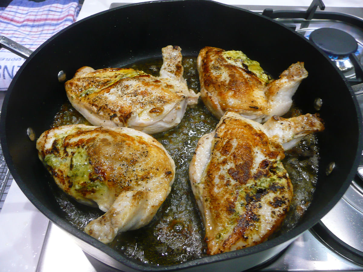 Grilled chicken breast with basil and parmesan sauce - sizzling in the pan