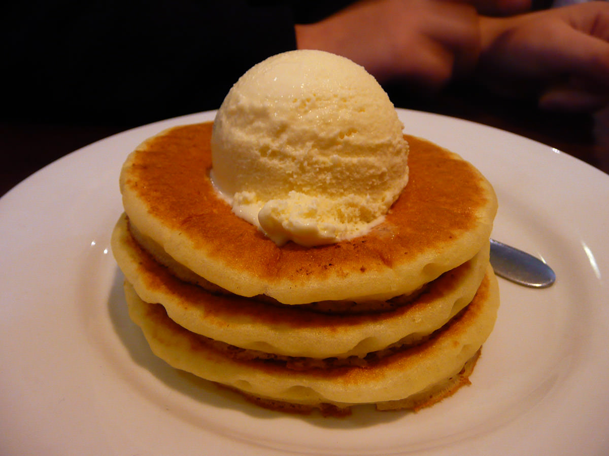 Mini pancake stack topped with a scoop of vanilla ice cream