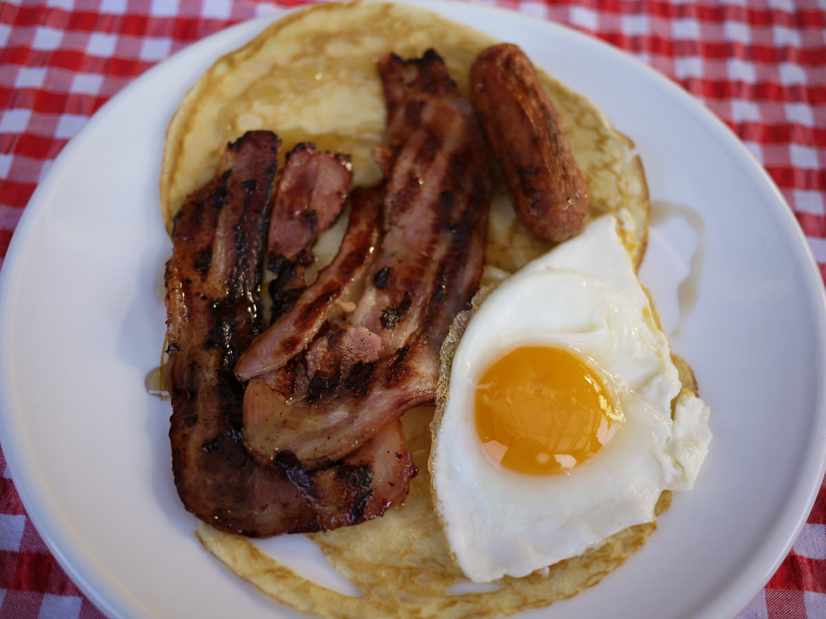Pancakes with bacon, sausage, egg and maple syrup