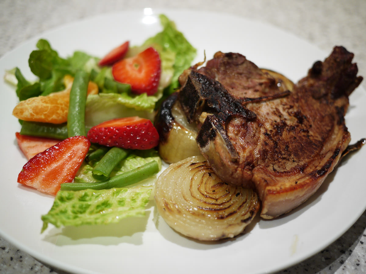 Grilled pork chop and onions with salad