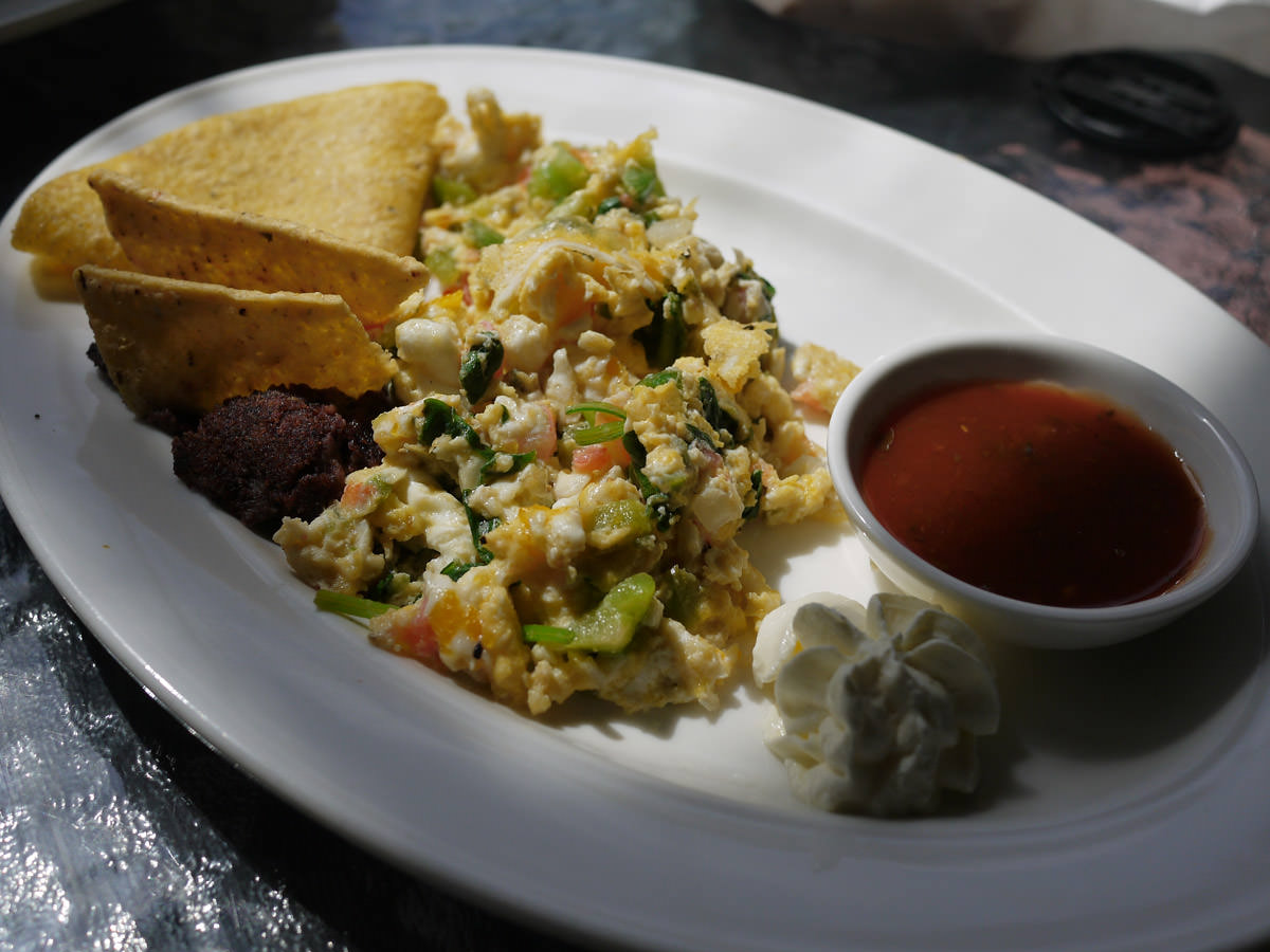 Spicy scrambled eggs served with refried beans and corn tortilla