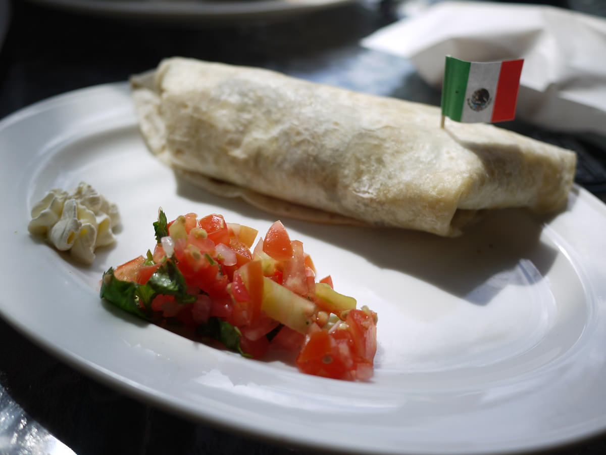 Breakfast burrito, complete with sour cream, salsa and Mexican fla
