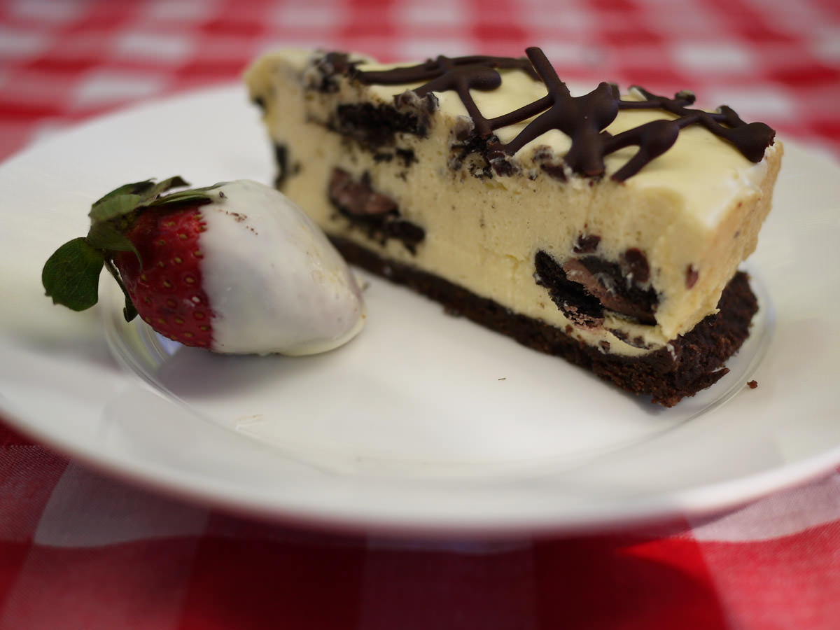 A slice of birthday cheesecake with a white chocolate-dipped strawberry