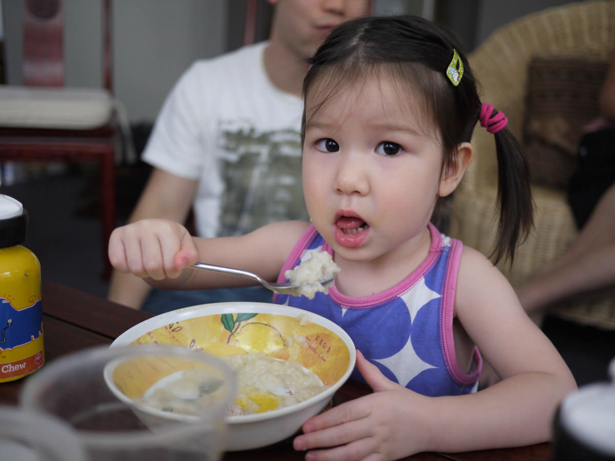 Zoe eating rice porridge