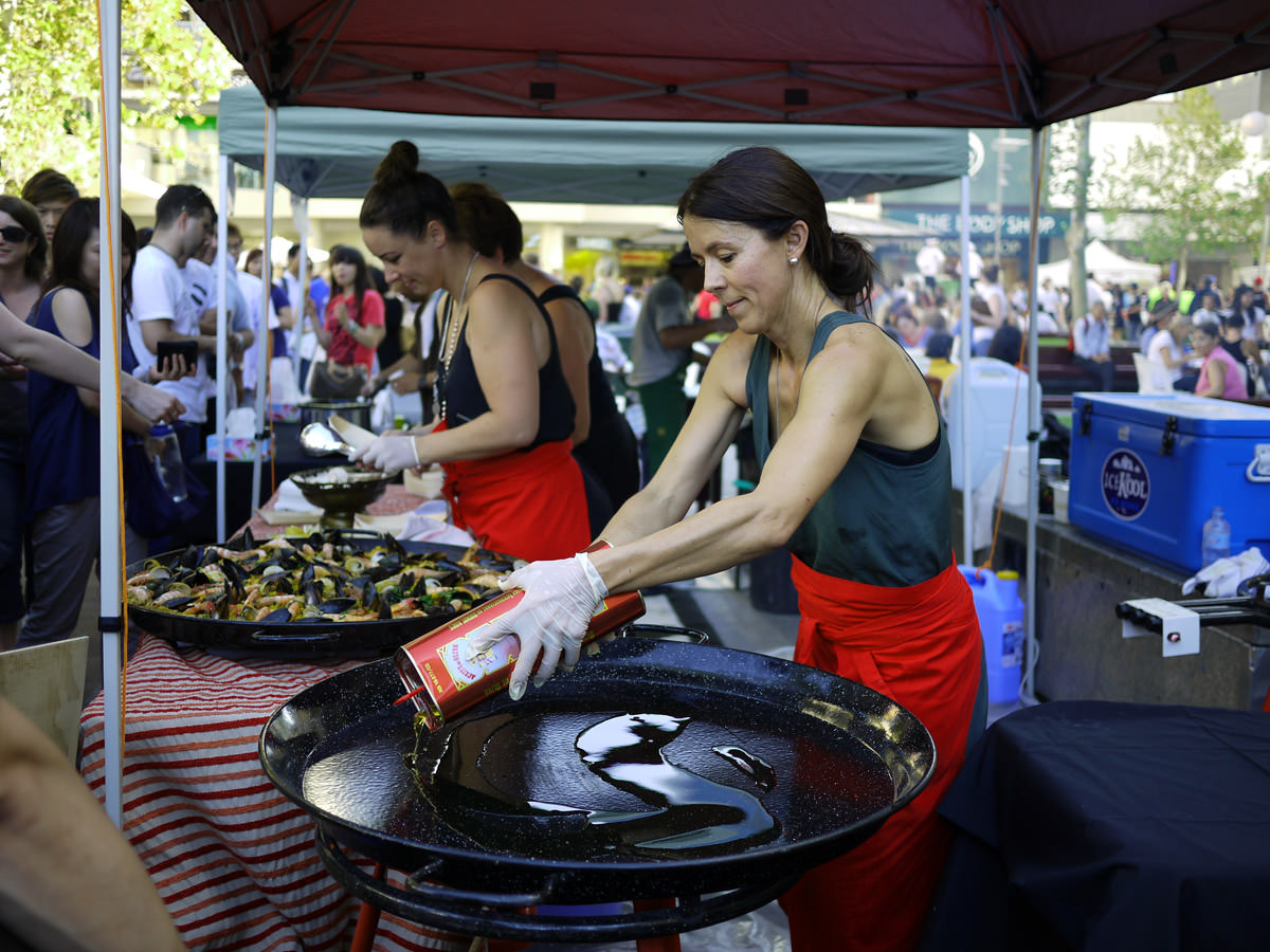 Serving up the first batch of paella, preparing the second batch