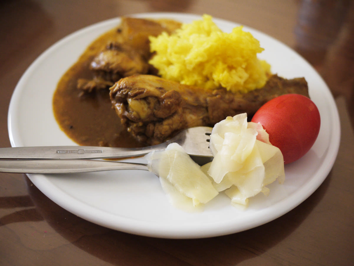 Jac's plate: Chicken curry, yellow rice, red egg and pickled ginger