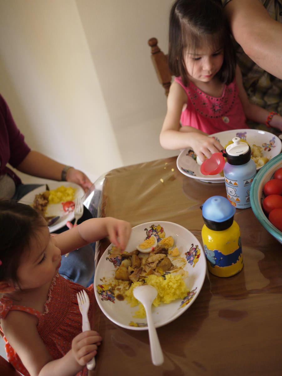 The girls eat chicken curry and rice with red eggs