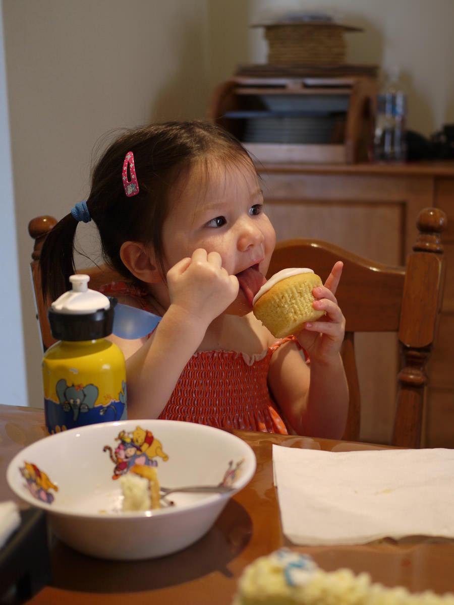 Zoe licks the lemon icing on cupcake
