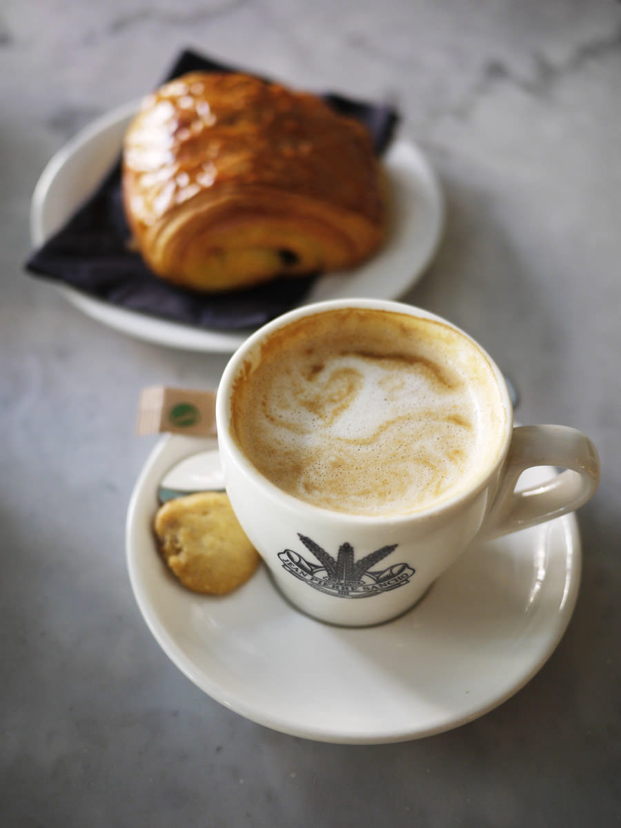 Chocolate croissant with a flat white