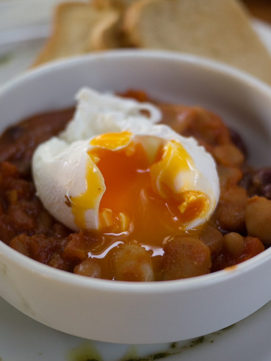 A perfectly gooey poached egg on baked beans