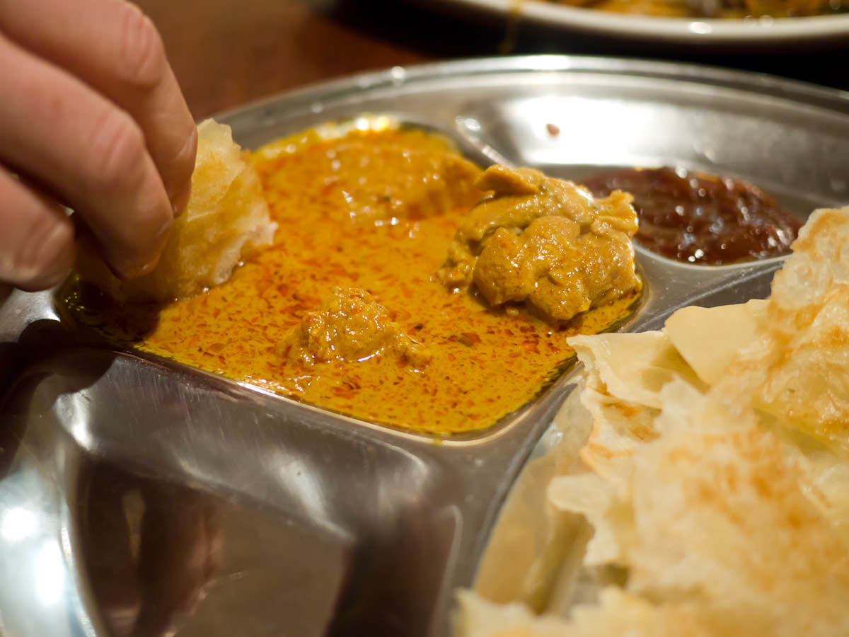 Dipping roti canai into curry chicken
