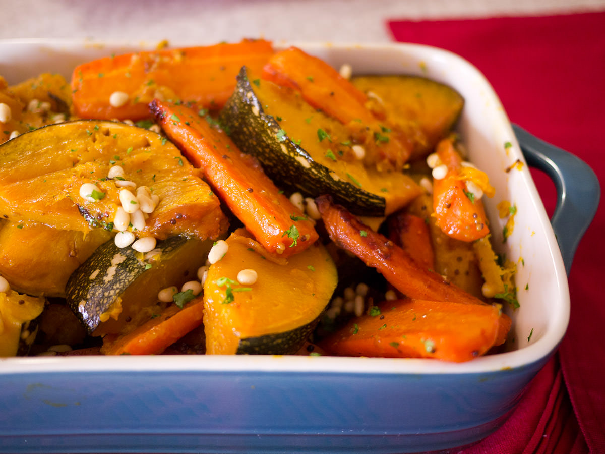 Roasted pumpkin and carrot sprinkled with pine nuts