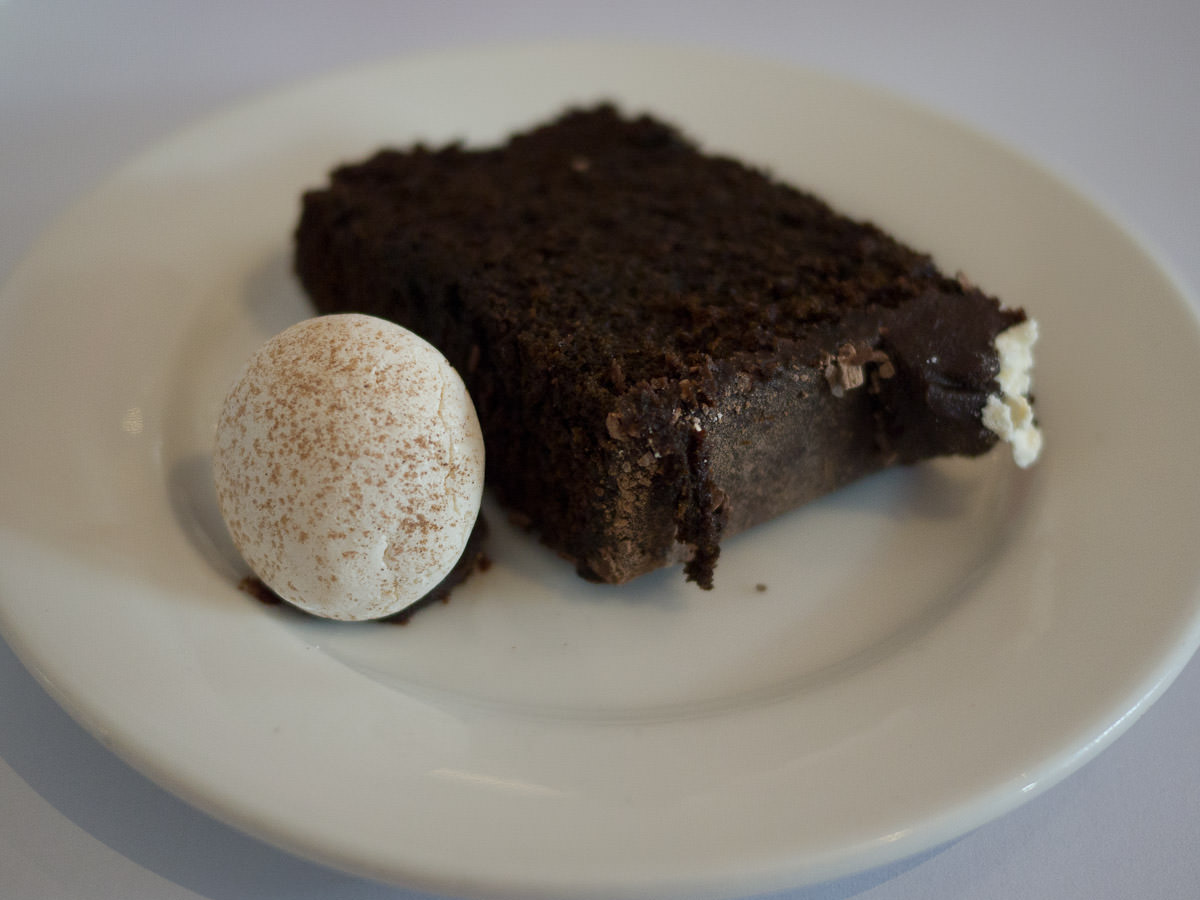A piece of chocolate cake with a meringue mushroom