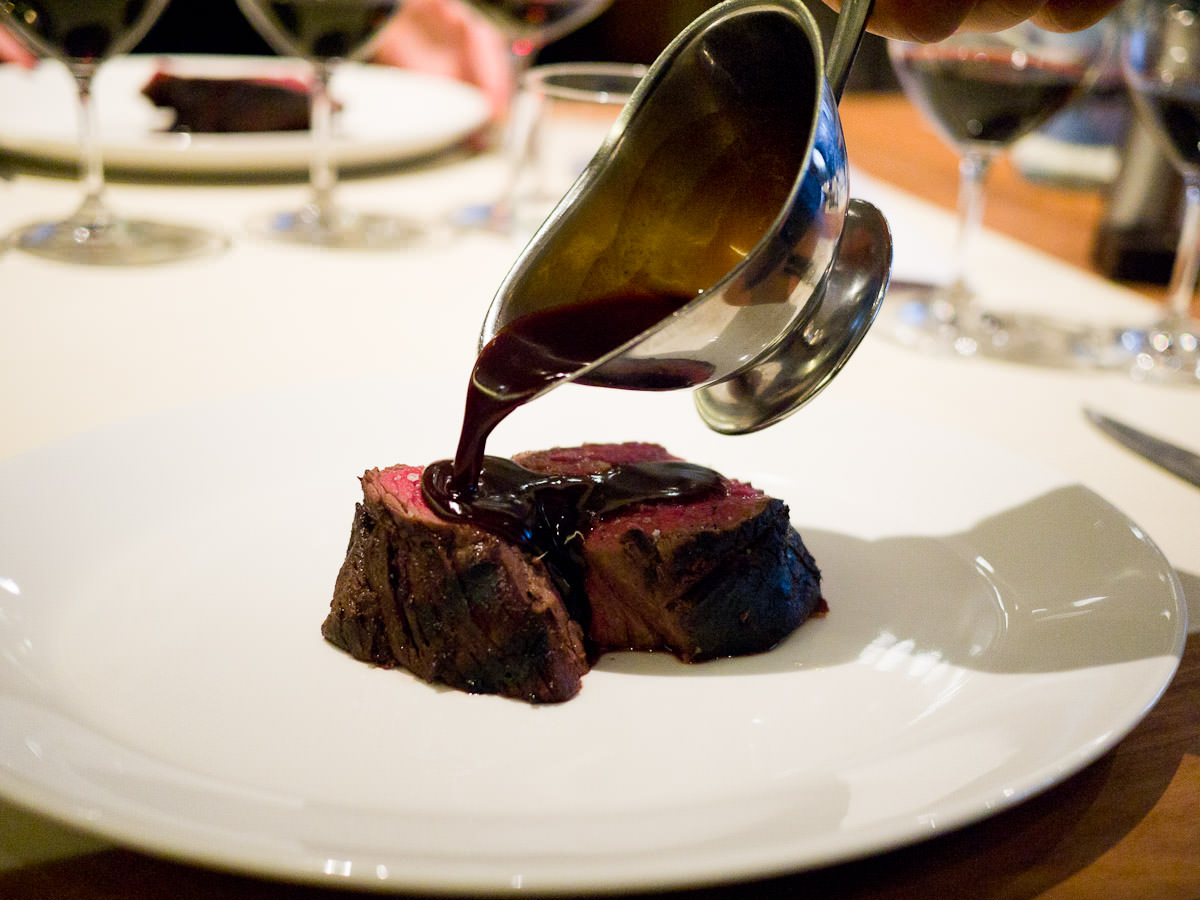 Red wine sauce being poured over slow cooked charred Rangers Valley beef fillet