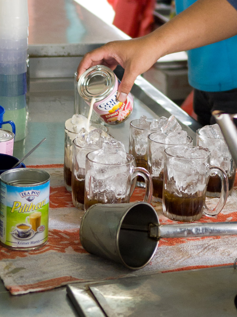 Adding condensed milk to the ice and tea