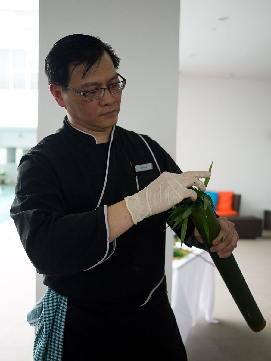 Stuffing young tapioca leaves into the bamboo tube that's been filled with the chicken mixture