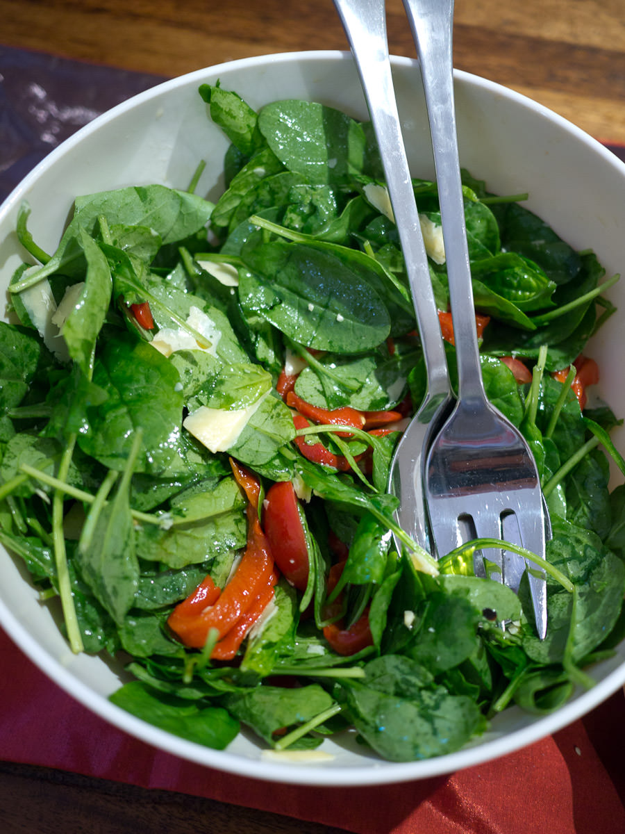 Spinach salad with mini roma tomatoes, roasted capsicum and parmesan