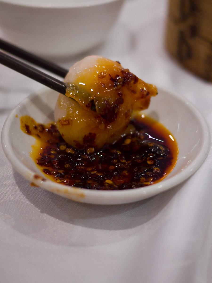 Charlene chilli-dipping a prawn dumpling