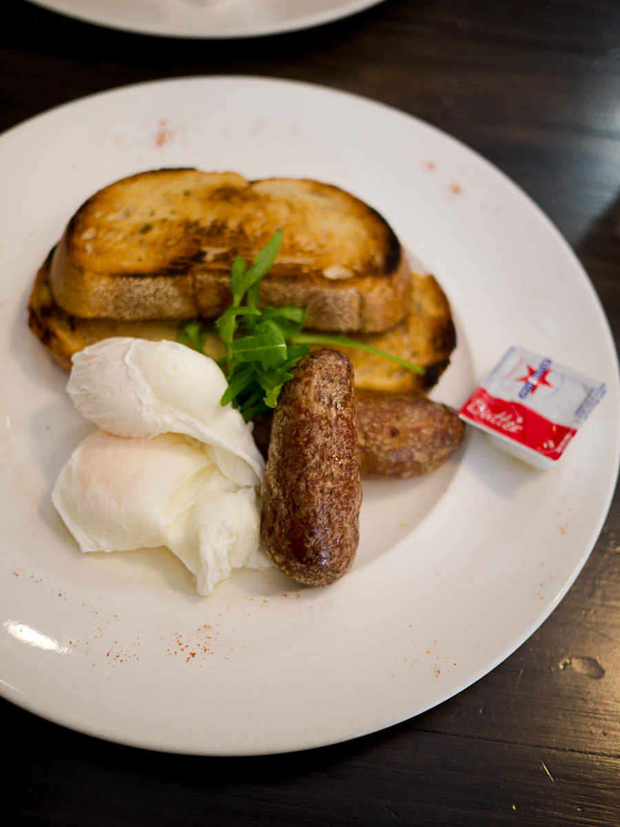 Poached free range eggs on toasted sour dough (AU$8) with pork sausage (AU$4)